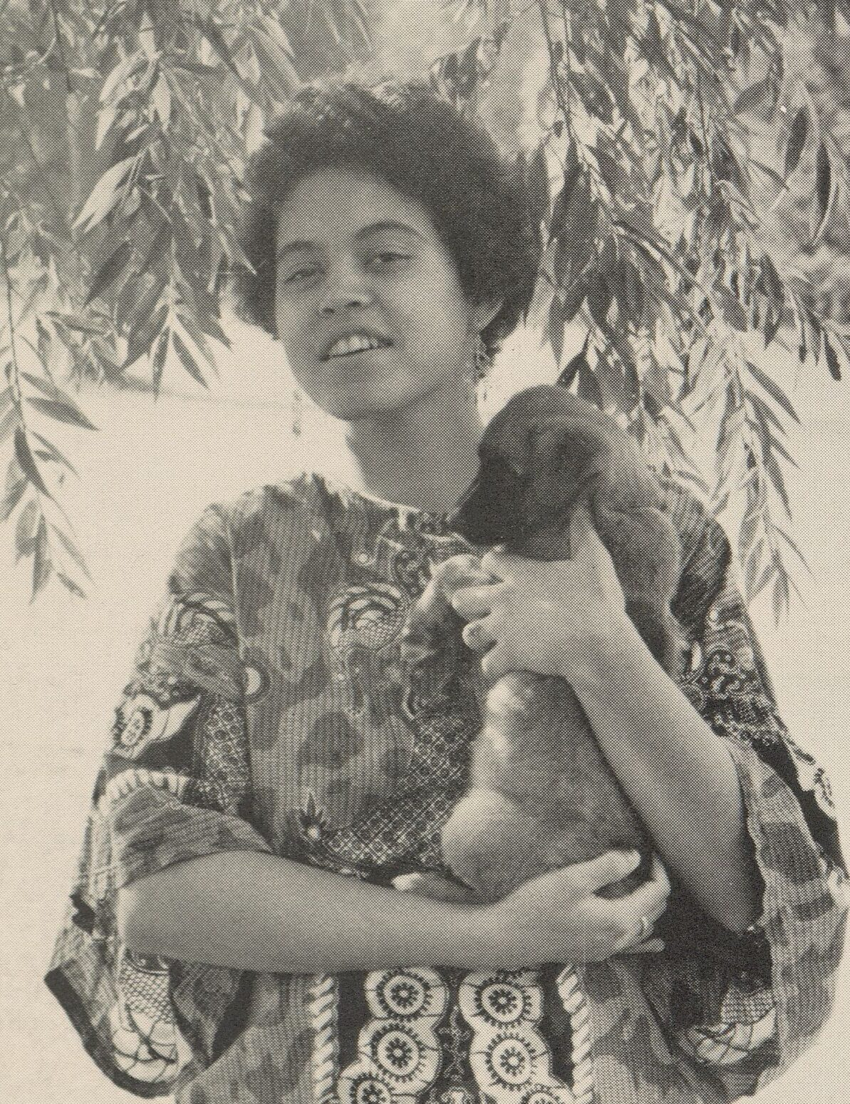 Yearbook photograph of Mindy Thompson. She wears a dashiki and Afro and is smiling and holding a small dog.